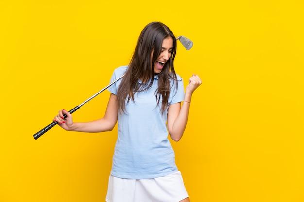 Femme jeune golfeur sur mur jaune isolé célébrant une victoire Photo Premium