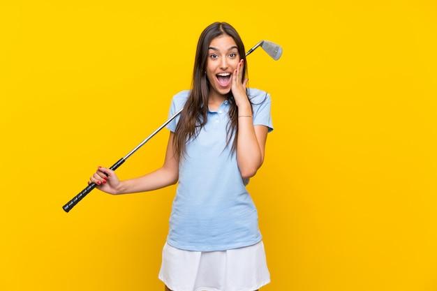 Femme jeune golfeur sur mur jaune isolé avec expression faciale surprise et choquée Photo Premium