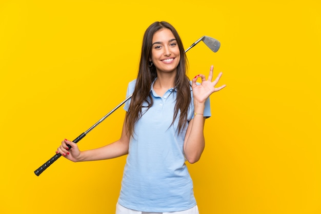 Femme jeune golfeur sur mur jaune isolé, montrant un signe ok avec les doigts Photo Premium