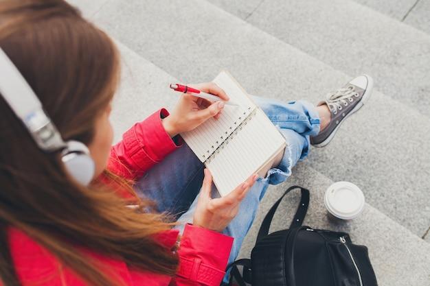 Femme Jeune Hipster En Manteau Rose, Jeans Assis Dans La Rue Avec Sac à Dos Et Café En écoutant De La Musique Au Casque Photo gratuit