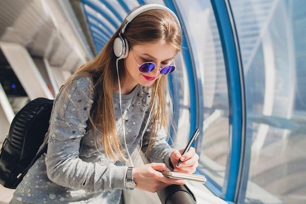 Femme Jeune Hipster En Tenue Décontractée S'amusant à écouter De La Musique Au Casque Photo gratuit
