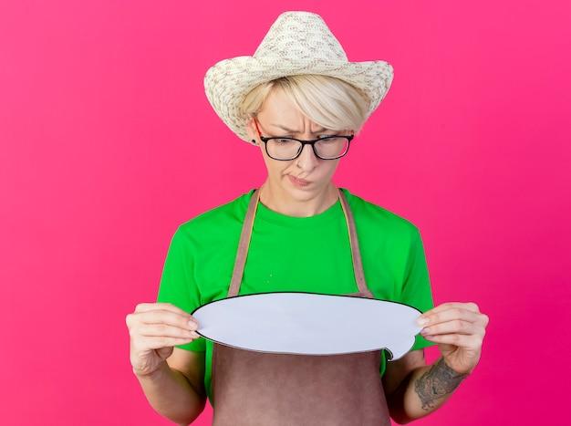 Femme Jeune Jardinier Aux Cheveux Courts En Tablier Et Chapeau Tenant Une Bulle De Dialogue Vierge Photo gratuit