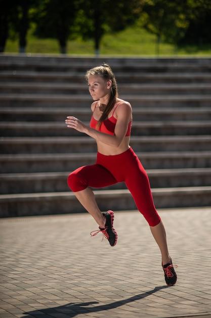 Femme jeune de remise en forme en cours d'exécution dans le stade. le concept d'un mode de vie sain Photo Premium