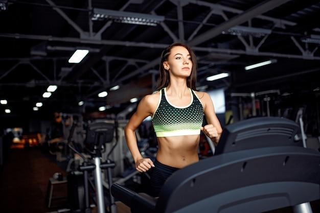 Femme Jeune De Remise En Forme, Faire Des Exercices De Cardio Au Gymnase En Cours D'exécution Sur Un Tapis Roulant. Photo Premium