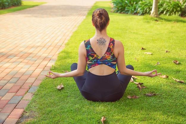 Femme jeune de remise en forme pratique l'yoga dans le parc. mode de vie sain et actif, thème du sport. Photo Premium