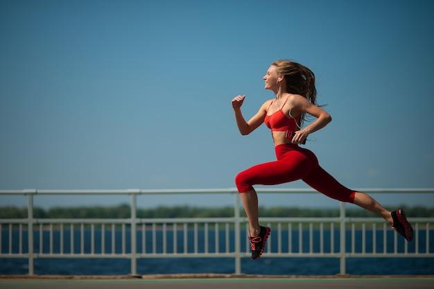 Femme jeune de remise en forme qui court sur la côte. le concept d'un mode de vie sain Photo Premium