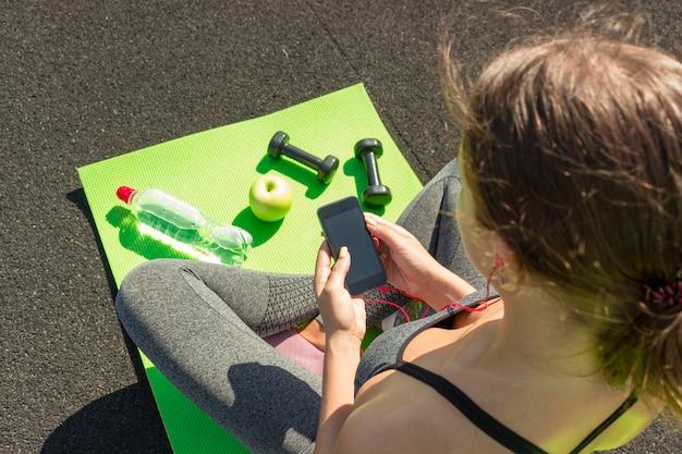 Femme Jeune Sport Sur Stade à L'aide De Smartphone. Photo Premium