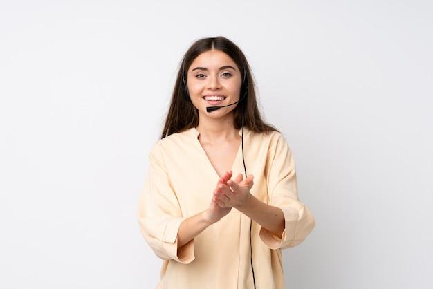 Femme jeune télévendeur au blanc isolé applaudissant Photo Premium