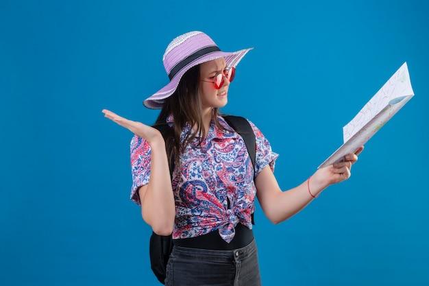 Femme Jeune Voyageur En Chapeau D'été Portant Des Lunettes De Soleil Rouges Tenant La Carte En La Regardant Confondu Avec Bras Ouvert Aucune Idée De Concept Debout Sur Fond Bleu Photo gratuit
