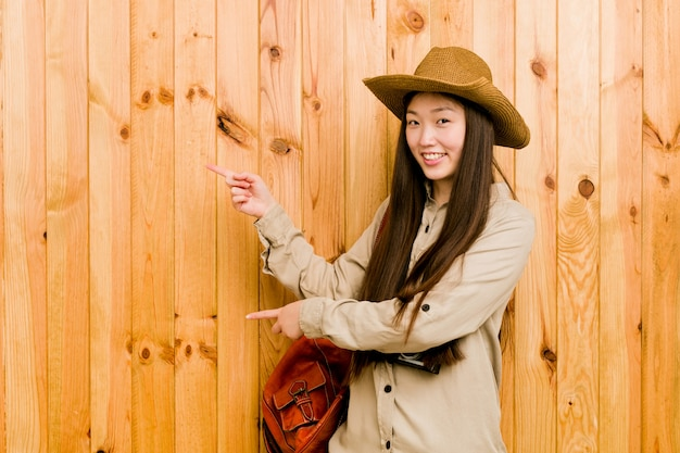 Femme jeune voyageur chinois excité pointant avec les index avant. Photo Premium
