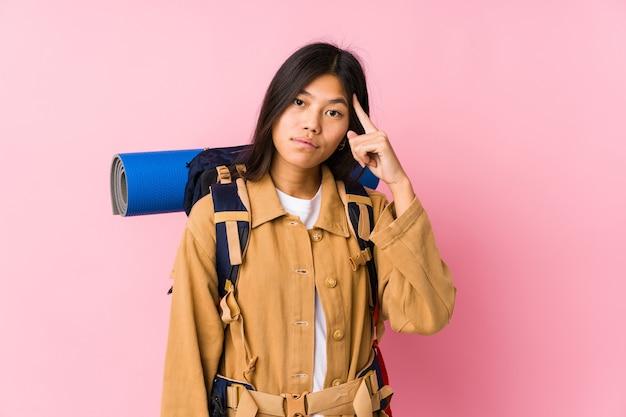 Femme Jeune Voyageur Chinois Isolé Temple De Pointage Avec Le Doigt, Pensant, Concentré Sur Une Tâche. Photo Premium