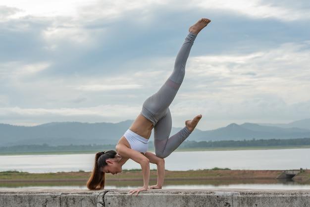 Femme de jeunes sportifs faire du yoga sur le lac avec fond de montagne. Photo Premium