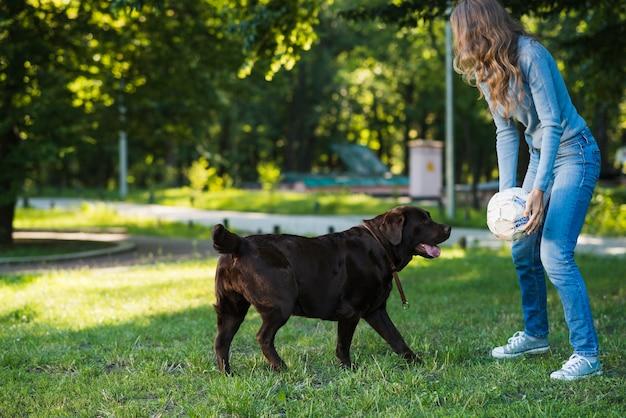 Femme jouant au foot avec son chien dans le jardin Photo gratuit