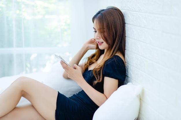La femme jouant au téléphone en souriant Photo Premium