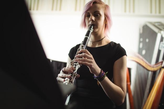Femme jouant de la clarinette à l'école de musique Photo gratuit