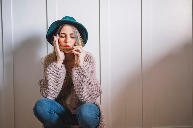 Femme jouant de l'harmonica près de mur blanc Photo gratuit