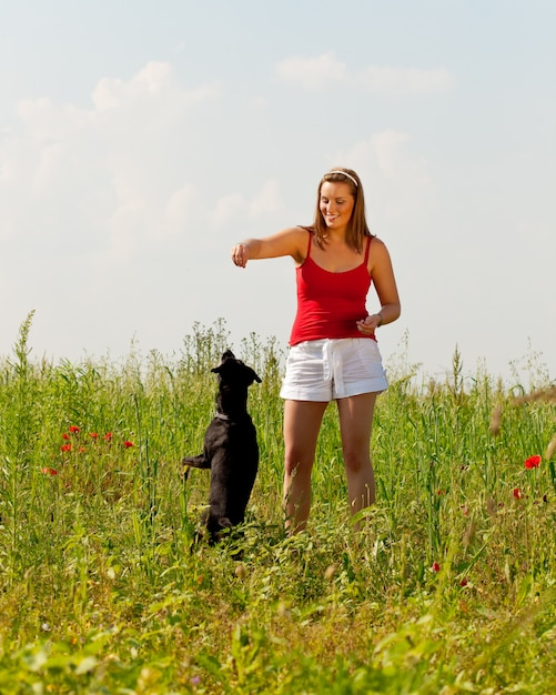 Femme jouant avec son chien dans un pré Photo Premium