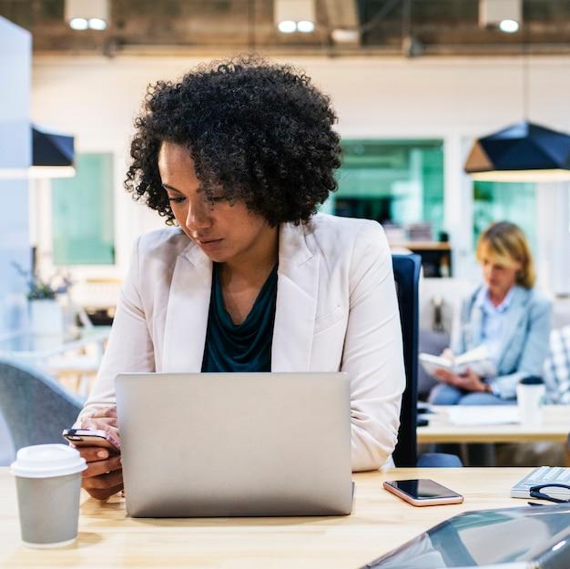 Femme jouant sur son téléphone au travail Photo gratuit