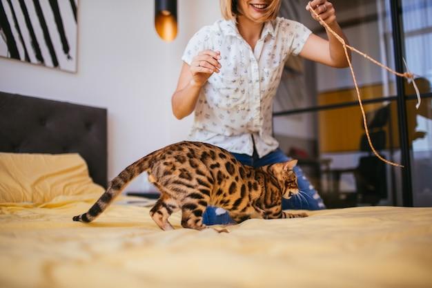 Femme joue avec une corde avec un chat bengal Photo gratuit