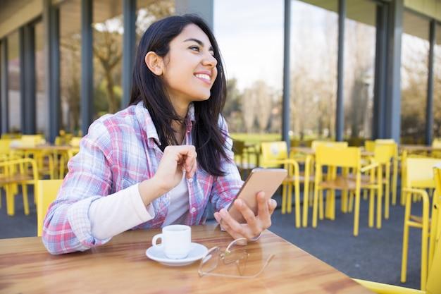 Femme joyeuse à l'aide de smartphone et de boire du café au café Photo gratuit