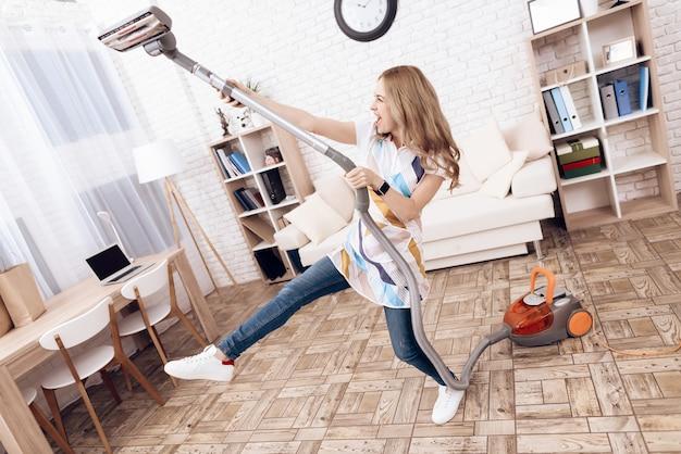 Femme joyeuse avec aspirateur dans l'appartement. Photo Premium