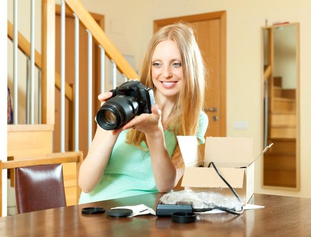 Femme joyeuse avec les cheveux blonds déballage pour nouvel appareil photo numérique à la maison Photo gratuit