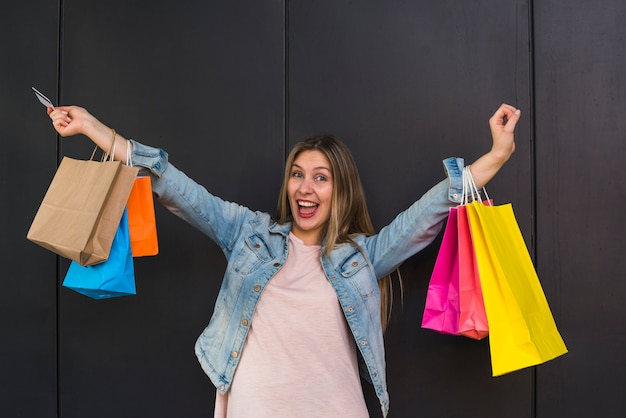 Femme joyeuse debout avec des sacs colorés Photo gratuit