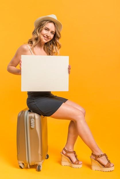 Femme joyeuse avec du papier vierge assis sur une valise Photo gratuit
