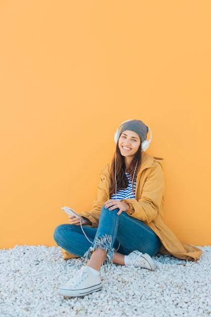 Femme joyeuse écoute la musique sur un téléphone intelligent assis sur un tapis contre une surface jaune Photo gratuit
