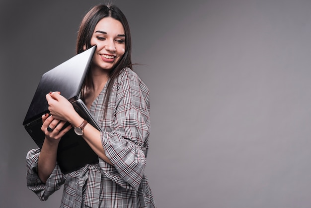 Femme joyeuse étreindre un ordinateur portable Photo gratuit