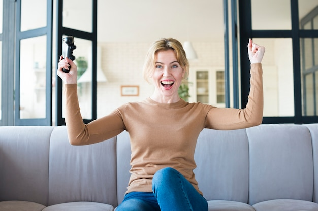 Femme joyeuse avec joystick sur canapé Photo gratuit