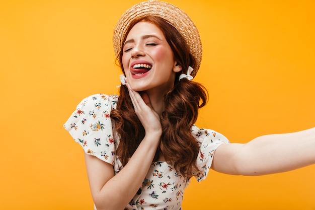 Femme Joyeuse En Plaisancier Montre Sa Langue Et Pose Pour Selfie Sur Fond Orange. Photo gratuit