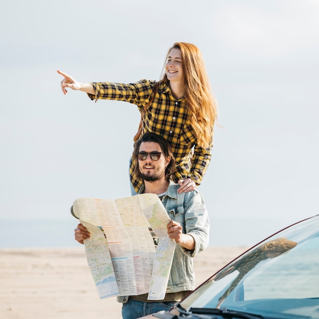 Femme joyeuse pointant près de l'homme regardant la carte près de la voiture Photo gratuit