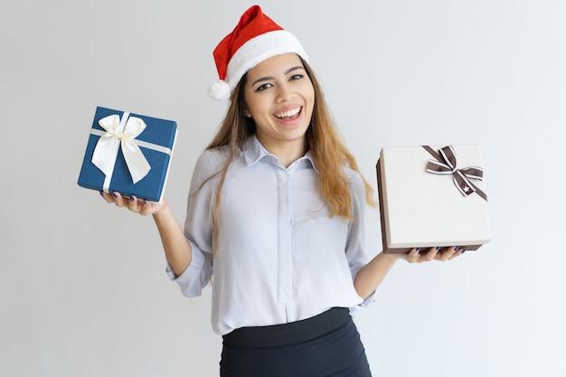 Femme joyeuse portant un chapeau de père noël et montrant des boîtes-cadeaux Photo gratuit