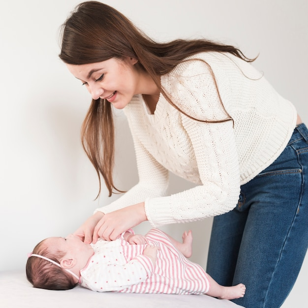 Femme joyeuse en prenant soin de bébé Photo gratuit