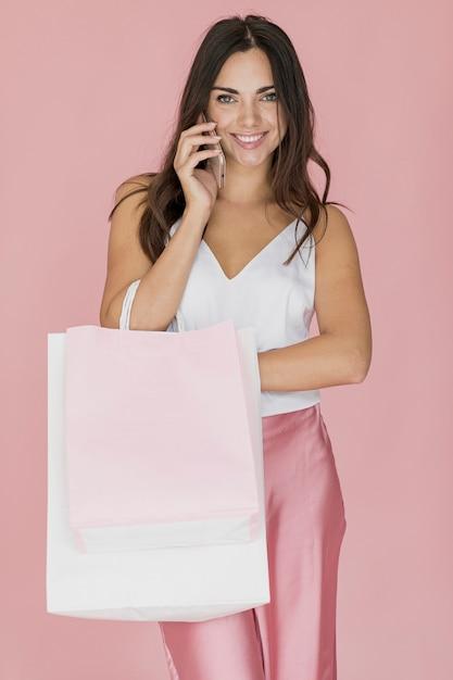 Femme joyeuse avec sac à provisions parlant sur smartphone Photo gratuit