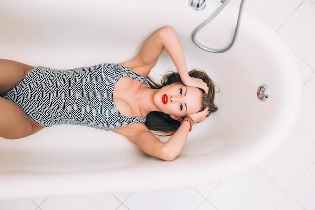 Une Femme Joyeuse Se Trouve Dans Une Baignoire En Mousse Blanche Reposant Une Peau Propre Photo gratuit