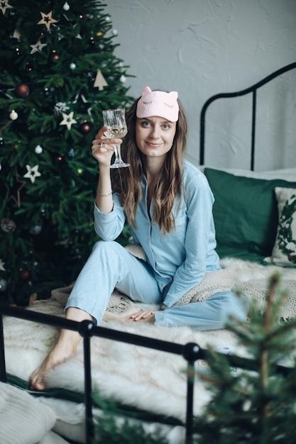 Femme Joyeuse Souriante En Pyjama Bleu Et Masque De Sommeil Assis Sur Le Lit Avec Une Coupe De Champagne. Noël. Photo gratuit