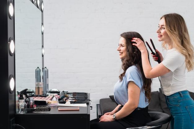 Femme joyeuse avec styliste faisant coiffure en studio Photo gratuit