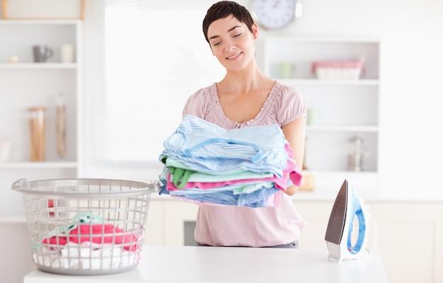 Femme joyeuse avec un tas de vêtements Photo Premium