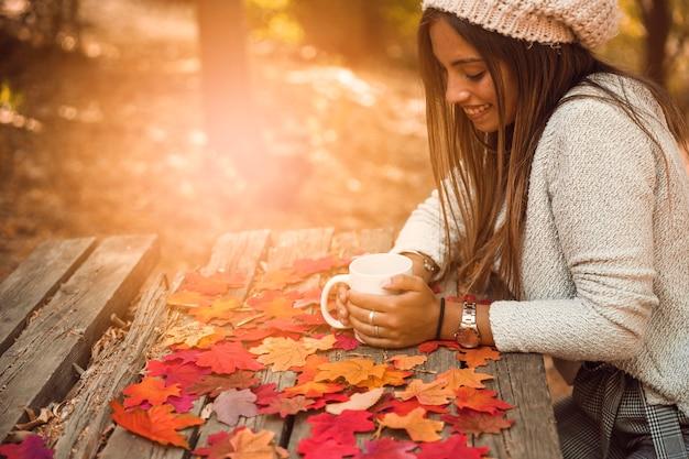 Femme joyeuse avec une tasse à table dans la partie automne Photo gratuit