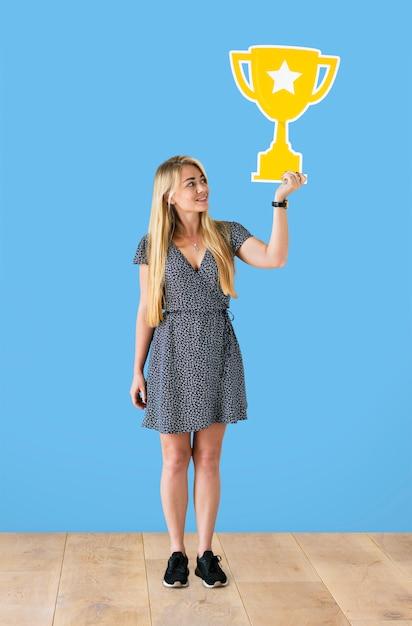 Femme joyeuse tenant une icône de trophée Photo gratuit