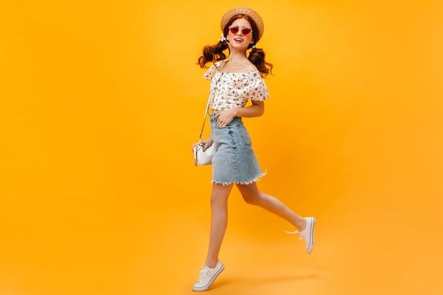 Femme En Jupe En Jean, T-shirt Blanc Et Canotier Sautant Sur Fond Orange. Femme à Lunettes De Soleil Souriant. Photo gratuit