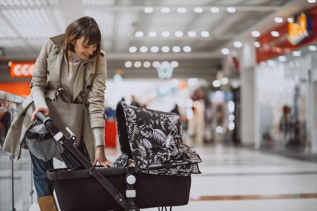Femme avec un landau dans un centre commercial Photo gratuit