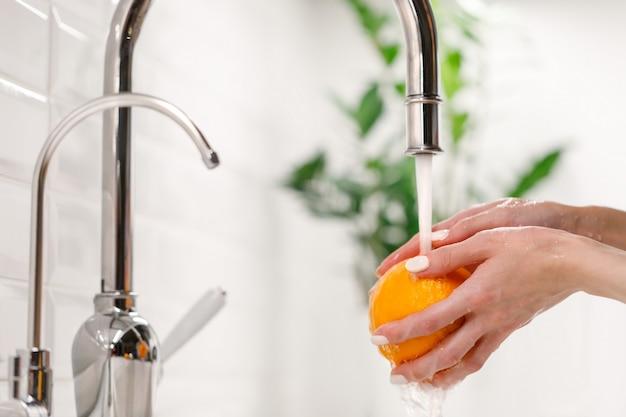 Femme Lavant L'orange Mûre Sous Le Robinet Dans La Cuisine De L'évier. Photo Premium
