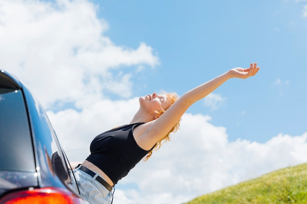 Femme levant la main au ciel par la fenêtre de la voiture par une journée ensoleillée Photo gratuit