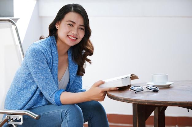 Femme lisant au café Photo gratuit