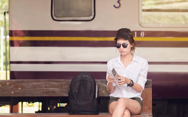 Femme lisant des brochures pour voyager. femme asiatique assise à la gare. Photo Premium