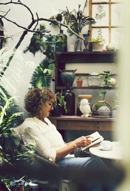 Femme lisant un livre dans un café Photo Premium