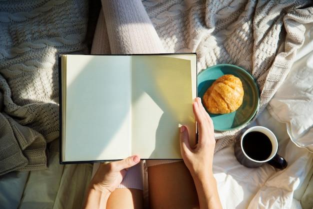 Femme lisant un livre roman sur le lit petit déjeuner Photo Premium